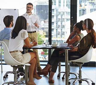 Man giving a whiteboard presentation to colleagues in a boardroom